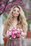 Πανέμορφο πορτρέτο ενός ξανθού κοριτσιού σε ένα προκλητικό ρόδινο φόρεμα βραδιού με μια ανθοδέσμη των όμορφων τριαντάφυλλων στοκ εικόνες