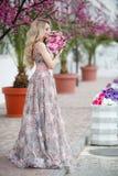 Πανέμορφο πορτρέτο ενός ξανθού κοριτσιού σε ένα προκλητικό ρόδινο φόρεμα βραδιού με μια ανθοδέσμη των όμορφων τριαντάφυλλων στοκ φωτογραφίες