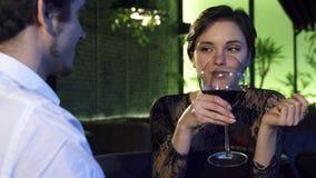 Πανέμορφο σκοτεινό μαλλιαρό κρασί κατανάλωσης γυναικών κατά τη διάρκεια της ημερομηνίας με το φίλο της απόθεμα βίντεο