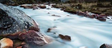 Πανέμορφο τυρκουάζ ρεύμα βουνών με τους κόκκινους βράχους Στοκ Φωτογραφία