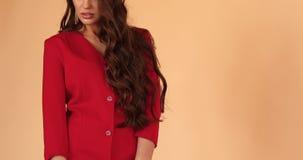 Πανέμορφο brunette στο προκλητικό κόκκινο φόρεμα που χορεύει στο στούντιο φιλμ μικρού μήκους