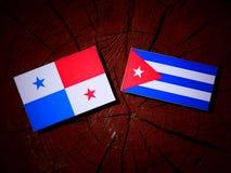 Παναμαία σημαία με την κουβανική σημαία σε ένα κολόβωμα δέντρων που απομονώνεται Στοκ Φωτογραφία