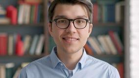 Πανεπιστήμιο βιβλιοθηκών ραφιών χαμόγελου σπουδαστών νεαρών άνδρων πορτρέτου φιλμ μικρού μήκους