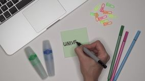 Πανεπιστήμιο γραψίματος χεριών γυναίκας στο σημειωματάριο Lap-top και χαρτικά στον πίνακα απόθεμα βίντεο