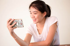 Πανεπιστημιακό όμορφο κορίτσι σπουδαστών της Ασίας ταϊλανδικό Κίνα που χρησιμοποιεί το έξυπνο τηλέφωνό της Selfie Στοκ Φωτογραφία