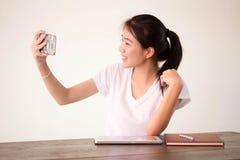 Πανεπιστημιακό όμορφο κορίτσι σπουδαστών της Ασίας ταϊλανδικό Κίνα που χρησιμοποιεί το έξυπνο τηλέφωνό της Selfie Στοκ εικόνα με δικαίωμα ελεύθερης χρήσης