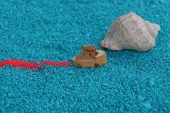 Πανιά παιχνιδιών βαρκών στην άμμο με ένα κοχύλι Στοκ εικόνες με δικαίωμα ελεύθερης χρήσης