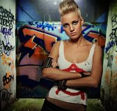 Πανκ κορίτσι με χρωματισμένη τη γκράφιτι πύλη πίσω από την στοκ φωτογραφίες