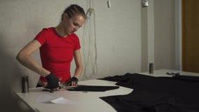 Πανκ σχεδιαστής μόδας Cyber στην εργασία στο τέμνον σχέδιο στούντιό της - καυκάσια λευκή γυναίκα που φορούν την κόκκινη μπλούζα κ φιλμ μικρού μήκους