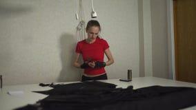 Πανκ σχεδιαστής μόδας Cyber στην εργασία στο τέμνον σχέδιο στούντιό της - καυκάσια λευκή γυναίκα που φορούν την κόκκινη μπλούζα κ απόθεμα βίντεο