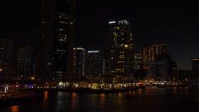 Πανοραμική άποψη από τον περίπατο στην πόλη νύχτας και τους υψηλούς ουρανοξύστες στη μαρίνα του Ντουμπάι απόθεμα βίντεο