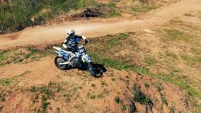 Πανοραμική άποψη ενός μοτοσυκλετιστή με το ποδήλατό του σε έναν λόφο Εναέριος επικός πυροβολισμός απόθεμα βίντεο