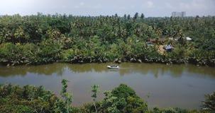 Πανοραμική άποψη κηφήνων του όμορφου ποταμού τροπικών δασών που ρέει στην αγριότητα ζουγκλών με τη μικρή βάρκα και τα τροπικά πρά απόθεμα βίντεο
