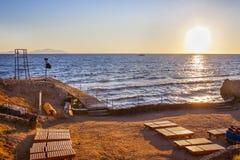 Πανοραμική άποψη μιας κενής αμμώδους παραλίας με τα sunbeds και το ηλιοβασίλεμα πέρα από τη θάλασσα Τα σύνολα ήλιων πίσω από τον  στοκ φωτογραφία
