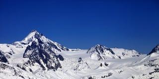 Πανοραμική άποψη σχετικά με τα βουνά χειμερινού Καύκασου στη συμπαθητική ημέρα ήλιων Στοκ Φωτογραφίες