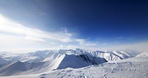 Πανοραμική άποψη σχετικά με τα χιονώδη βουνά στη συμπαθητική ημέρα Στοκ Εικόνα