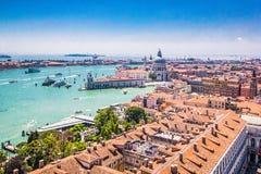 Πανοραμική άποψη της Βενετίας - χαιρετισμός della της Σάντα Μαρία βασιλικών, μεγάλο κανάλι με τις γόνδολες και τις κόκκινες κεραμ στοκ εικόνα