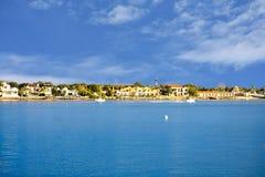 Πανοραμική άποψη του ζωηρόχρωμων σπιτιού, του φάρου και των βαρκών στο ανοικτό μπλε υπόβαθρο ουρανού στην ιστορική ακτή της Φλώρι στοκ εικόνα