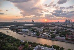 Πανοραμική άποψη του ηλιοβασιλέματος επάνω από τις αντανακλάσεις πόλεων και σύννεφων της Μόσχας στον ποταμό με τις διακινούμενες  Στοκ εικόνα με δικαίωμα ελεύθερης χρήσης