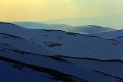 Πανοραμική άποψη του τοπίου βουνών κατά τη διάρκεια του ηλιοβασιλέματος, καθαρός άσπρος τομέας χιονιού, κίτρινος ουρανός, άσπρα σ στοκ εικόνα με δικαίωμα ελεύθερης χρήσης