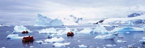 Πανοραμική άποψη των οικολογικών τουριστών στη διογκώσιμη Zodiac βάρκα με τους παγετώνες και των παγόβουνων στο λιμάνι παραδείσου Στοκ φωτογραφία με δικαίωμα ελεύθερης χρήσης