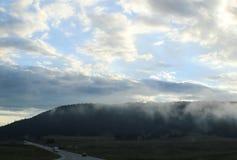 Πανοραμική άποψη των misty βουνών κάτω από το μεγάλο νεφελώδη ουρανό με τα αγροτικά κτήρια στον ορίζοντα και την κυκλοφορία στο δ Στοκ εικόνα με δικαίωμα ελεύθερης χρήσης