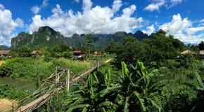 Πανοραμική αγροτική περιοχή στο Λάος με την ξύλινη γέφυρα που διασχίζει το riv Στοκ Εικόνες