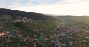 Πανοραμική ανατολή πυροβολισμού πέρα από τη μικρή πόλη σε μια δασώδη κοιλάδα απόθεμα βίντεο