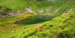 Πανοραμική φωτογραφία μιας λίμνης βουνών σε μια ορεινή δύσκολη κοιλάδα Γαλήνια λίμνη Berbeneskul, Carpathians, Ουκρανία Στοκ Εικόνες