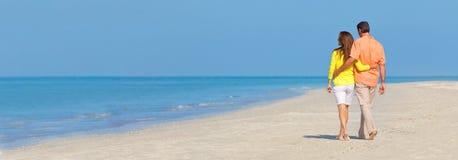 Πανοραμικό ζεύγος εμβλημάτων που περπατά σε μια κενή παραλία στοκ εικόνες