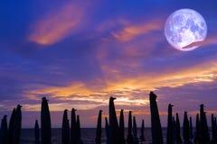 πανσέληνος στον ουρανό και το ηλιοβασίλεμα και η σκιά της ομπρέλας παραλιών στοκ φωτογραφία με δικαίωμα ελεύθερης χρήσης