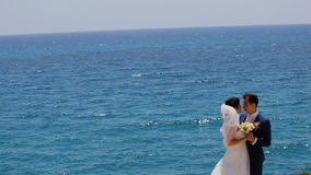 Παντρεμένος αγκαλιάζοντας σε ένα υπόβαθρο τη θάλασσα φιλμ μικρού μήκους