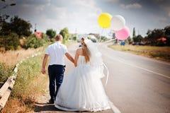 Παντρεμένο ζευγάρι με τον περίπατο μπαλονιών μαζί στο δρόμο Στοκ Φωτογραφία