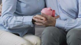 Παντρεμένο ζευγάρι που κρατά τη piggy τράπεζα στα χέρια, κατάλληλος προγραμματισμός οικογενειακών προϋπολογισμών φιλμ μικρού μήκους