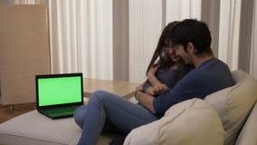 Παντρεμένο ζευγάρι που προσέχει έναν κινηματογράφο θρίλλερ στη διαβίωση, το δωμάτιο σε ένα lap-top με την πράσινη οθόνη που αγκαλ απόθεμα βίντεο