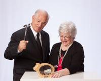 Παντρεμένο ζευγάρι που σπάζει την τράπεζα Piggy για την αποχώρηση στοκ εικόνα με δικαίωμα ελεύθερης χρήσης