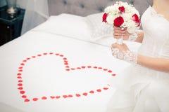 Παντρεψτε, γάμος Νύφη στο σπίτι Νυφικό κρεβάτι Μορφή καρδιών πετάλων Στοκ Εικόνα