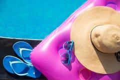 Παντόφλες, γυαλιά ηλίου, καπέλο αχύρου και στρώμα αέρα στοκ εικόνα