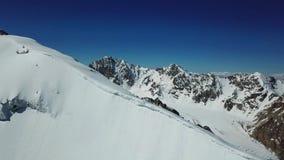Πανόραμα από έναν κηφήνα πέρα από έναν χιονώδη απότομο βράχο στα βουνά Δύο ορειβάτες αναρριχούνται στην αιχμή απόθεμα βίντεο