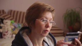 Πανόραμα από τα δώρα στη γυναίκα που χρησιμοποιεί το smartphone να ψωνίσει on-line με την πιστωτική κάρτα απόθεμα βίντεο