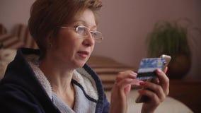 Πανόραμα από τα δώρα Χριστουγέννων στη γυναίκα που χρησιμοποιεί το smartphone να ψωνίσει on-line με την πιστωτική κάρτα απόθεμα βίντεο