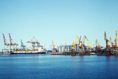 Πανόραμα ενός θαλάσσιου λιμένα με τους γερανούς φορτίου και ενός σκάφους με τα εμπορευματοκιβώτια φορτίου Στοκ Εικόνα