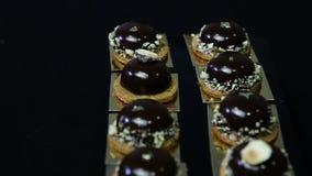 Πανόραμα κάτω στα μικρά στρογγυλά επιδόρπια σοκολάτας φιλμ μικρού μήκους