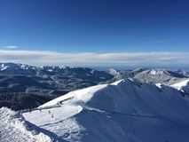Πανόραμα και μπλε ουρανός βουνών χιονιού Στοκ Φωτογραφία