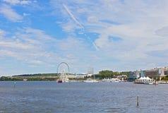 Πανόραμα με τις βάρκες, τα σύγχρονα κτήρια και το λιμάνι Ferris κάτω από τους υψηλούς ουρανούς με τα σύννεφα Στοκ Εικόνες