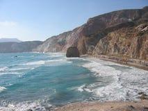 Πανόραμα μιας στενής παραλίας με τους χρωματισμένους βράχους και μιας κινούμενης θάλασσας του νησιού της Μήλου στην Ελλάδα στοκ εικόνα με δικαίωμα ελεύθερης χρήσης