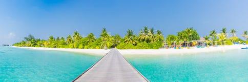 Πανόραμα παραλιών νησιών των Μαλδίβες Φραγμός φοινίκων και παραλιών και μακροχρόνια ξύλινη διάβαση αποβαθρών Έμβλημα τροπικών δια στοκ εικόνα με δικαίωμα ελεύθερης χρήσης