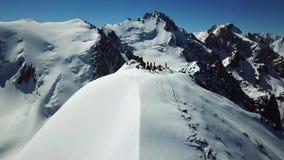 Πανόραμα της αιχμής με τους τουρίστες Το επίτευγμα του ύψους στόχου! Μπλε ουρανός και χιονώδη βουνά απόθεμα βίντεο