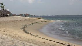 Πανόραμα της αμμώδους παραλίας με τα σαλόνια μονίππων και sunshades στο τροπικό θέρετρο πρεσών Ινδονησία απόθεμα βίντεο