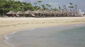Πανόραμα της αμμώδους παραλίας με τα σαλόνια μονίππων και sunshades στο τροπικό θέρετρο πρεσών Ινδονησία φιλμ μικρού μήκους